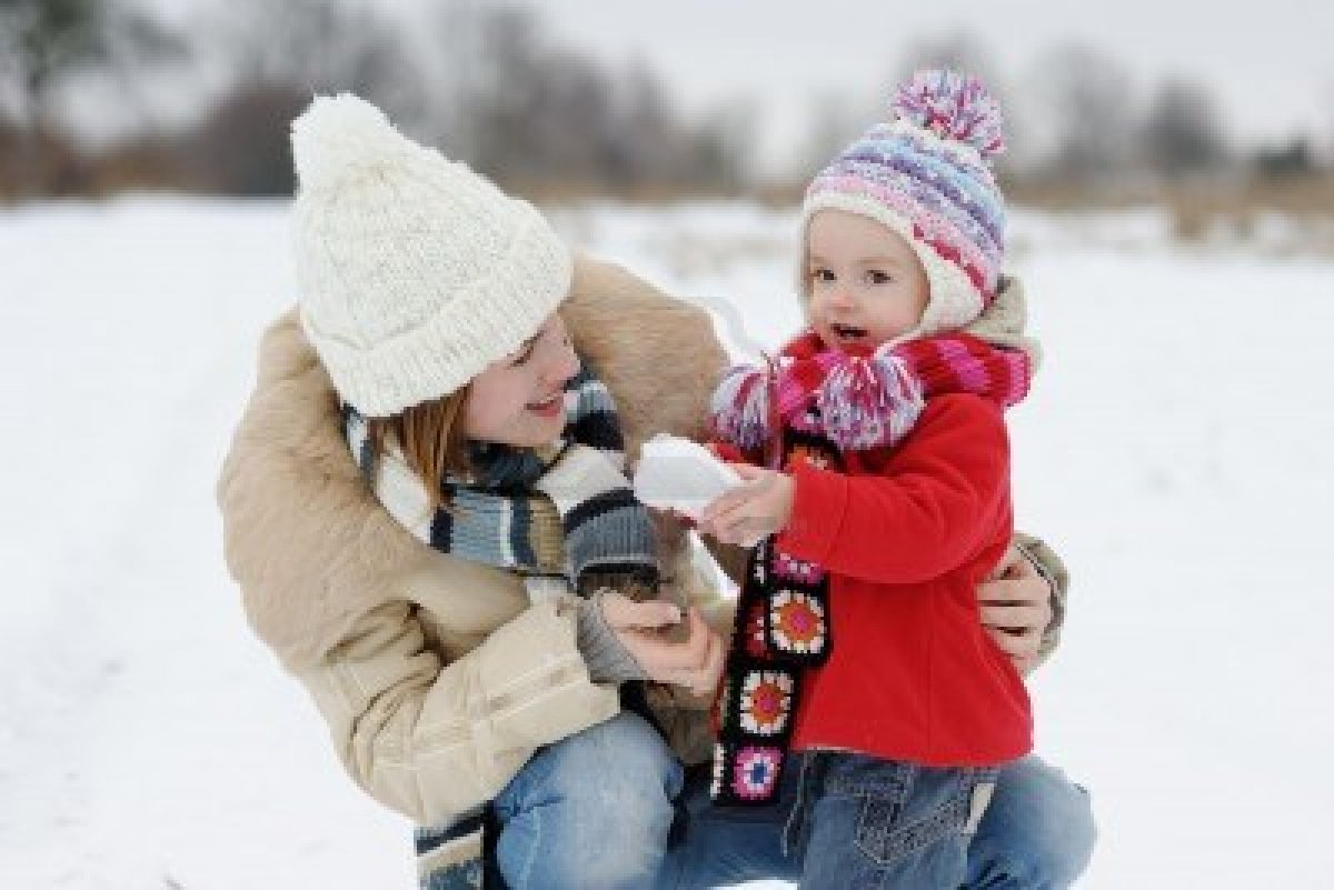 6226358 little winter baby girl and her mother making a snowball